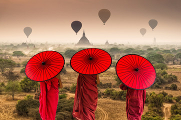 Back side of three Buddhist novice are walking over the Ancient Temples in Bagan with hot air on the sky at sunrise time, Myanmar Wall mural