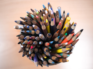 Detailed macro photograph view of the tops of a container of many sharpened colored art pencils from above.