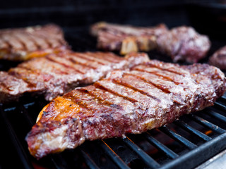Close-up photograph of various cuts of beef including filet mignon and t-bone steak on a gas fire grill for a backyard barbeque.