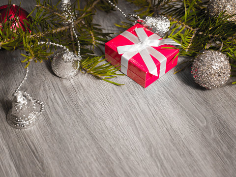 Close up photograph of a red small present wrapped in white ribbon laying on a gray wood grain floor with evergreen pine needle limb and silver ornaments in background.