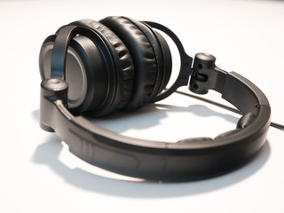 Close up photograph of black DJ style headphones isolated on a white background.