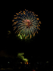 Gorgeous Independence day fourth of July real firework display exploding in the sky with vivid orange and blue colors with delicate feathered ends in a black night sky with smoke billowing below
