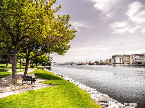 Beautiful landscape scenery shot along the Fox River just after sunrise in Green Bay Wiscosin with riverwalk trail, bench, trees, grass and rocky shoreline framing the shot and blue cloud filled sky.