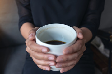 Closeup image of a woman's hands holding a white cup of hot coffee
