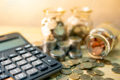 calculator with coin in currency glass jar and spilling on wooden