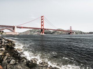 Golden Gate bridge with waves crashing against rocks in the foreground along the San Francisco Bay in California.