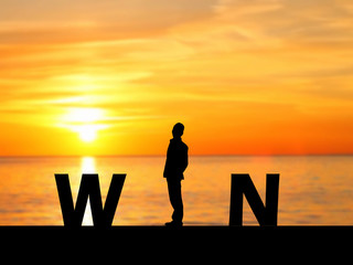 Silhouette business man on the beach and WIN message