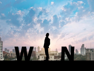 Silhouette business man on city background  and WIN message