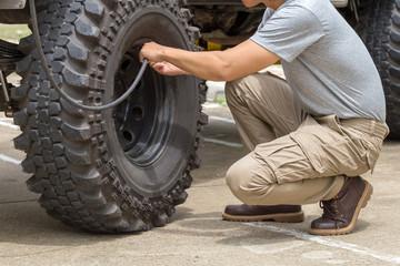 man pumps a offroad car wheel with a compressor.