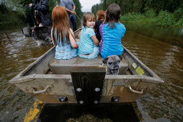Iva Williamson peers behind her as she joins neighbors and pets in fleeing rising flood waters in the aftermath of Hurricane Florence in Leland, North Carolina