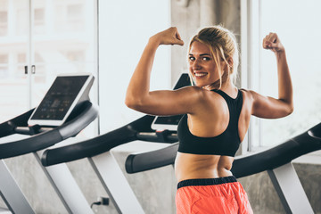 Portrait of Attractive young woman in sportswear showing her muscles at the gym