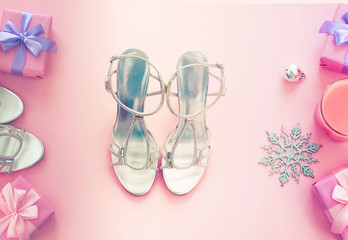 Christmas background pink Flat Lay fashion accessories sandals phone gift box bow balls purple.