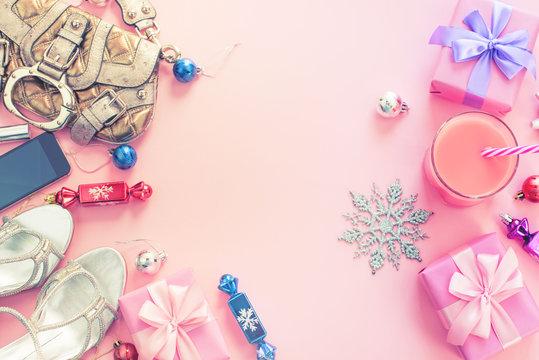 Christmas background pink Flat Lay fashion accessories handbag sandals phone gift box bow balls purple pink.