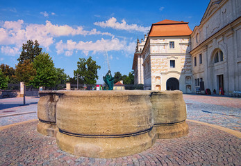Main gate to the Litomysl Castle. One of the largest Renaissance castles in the Czech Republic. A UNESCO World Heritage Site. Sgraffito painting in the walls.  Beautiful fountain in the foreground