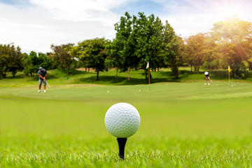 White Golf ball on tee ready to be shot on blurred beautiful landscape of golf course in bright day time with golfer playing golf on course. Sport, Recreation, Relax in holiday concept.