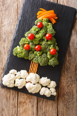 Beautiful food: Christmas tree of broccoli, cauliflower, tomatoes, pepper closeup. vertical top view