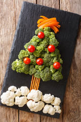 Christmas tree of broccoli, cauliflower, tomato, pepper closeup on table. Vegetarian. Vertical top view