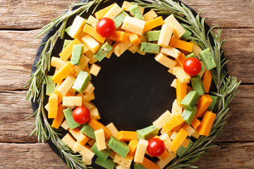 Christmas food: a wreath of pesto cheese, cheddar, mimolette with tomatoes and rosemary close-up. horizontal top view