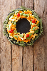 Assorted pesto cheese, cheddar, Mimolette with tomatoes and rosemary in the form of a wreath close-up. Vertical top view