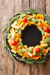 Beautiful Christmas appetizer of assorted cheese with tomato in the shape of a wreath close-up. Vertical top view