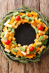 Christmas food: a wreath of pesto cheese, cheddar, mimolette with tomatoes and rosemary close-up. Vertical top view