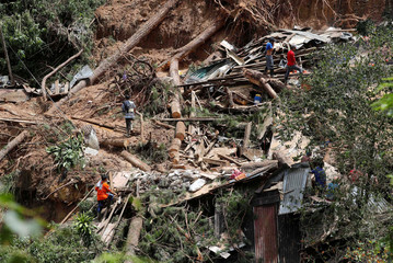 A view of debris and destroyed houses at the site of a landslide at a mining camp in Itogon