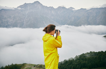 A young Girl in a yellow raincoat photographs the mountains. Georgia. Summer. August. Girl making a photo shoot of mountain.