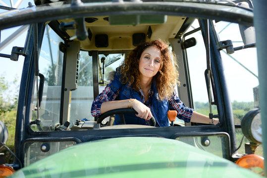 beautiful woman female farmer driving tractor in countryside field