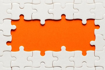 Wall Mural - White details of puzzle on orange background and place for inscription
