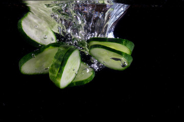pieces of sliced cucumber go to the bottom on a dark background