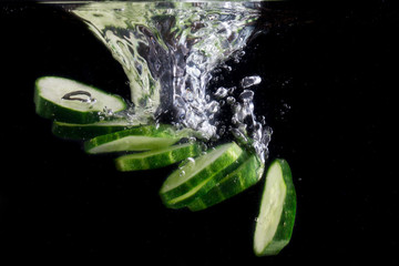 bright pieces of cucumber under water and a beautiful splash