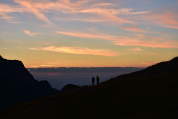 Young couple admiring the sunset in mountain. Ivan Vazov Hut, Rila Mountains, Bulgaria