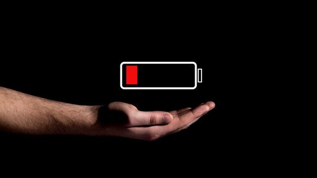 Hand showing Battery Charge icon on black background