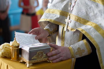 The hands of the priestly cross and the bible
