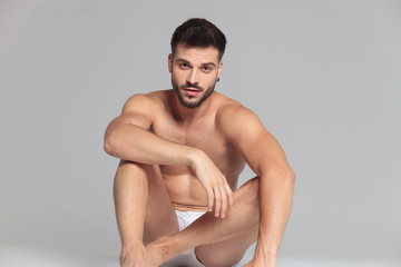 seated young man wearing only underwear is resting