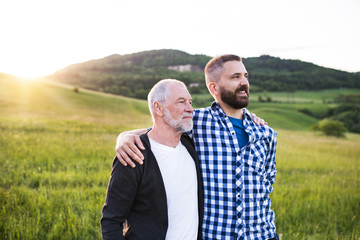 A portrait of an adult hipster son with senior father in nature at sunset, arms around each other. Wall mural