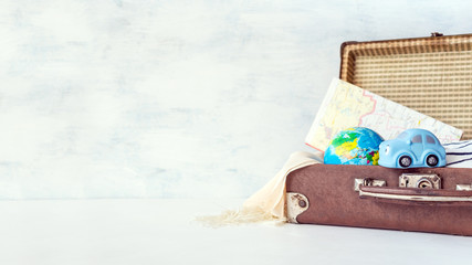 Travel, adventure, vacation concept. Brown retro suitcase with traveler set of travel booklets, maps, camera, clothes and blue toy car. How to Pack a Suitcase. Explore: Adventure Travel Holidays