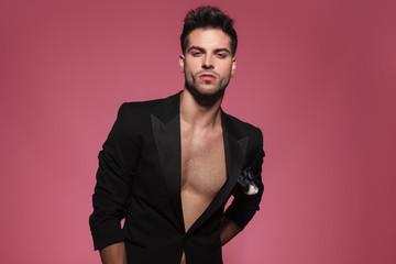 portrait of arrogant sexy man wearing only a black tuxedo