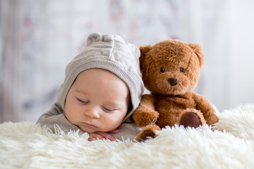 Sweet baby boy in bear overall, sleeping in bed with teddy bear Wall mural