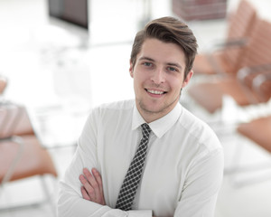confident young businessman on background of office
