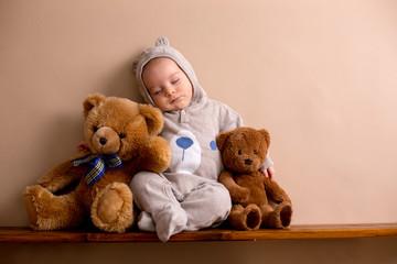 Sweet baby boy in bear overall, sleeping on a shelf with teddy bears