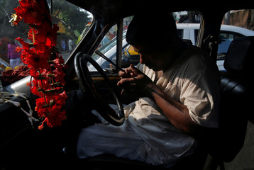 A priest offers prayer inside a taxi during the Vishwakarma Puja or the festival of the Hindu deity of architecture and machinery in Kolkata