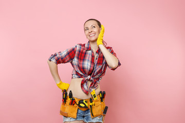 Strong young fun handyman woman in plaid shirt, denim shorts, yellow gloves, kit tools belt full of variety useful instruments isolated on pink background. Female doing male work. Renovation concept.