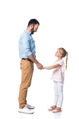 smiling father and daughter holding hands and looking at each other isolated on white