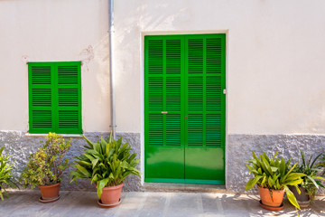 Green door and green window on old traditional house in Mallorca, Spain