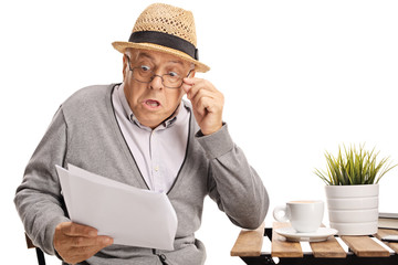 Shocked elderly man reading a document