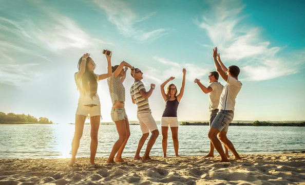 Happiness Friends funny  dance on the beach party under sunset sunlight