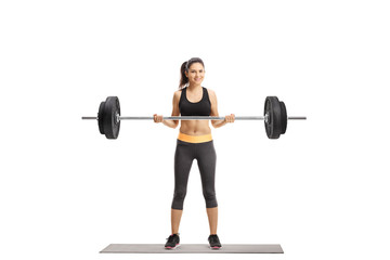 Young athletic female lifting a barbell