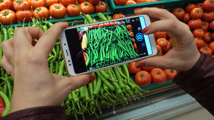 Hand taking picture of tomatoes and other vegetables using smart phone at grocery shop.