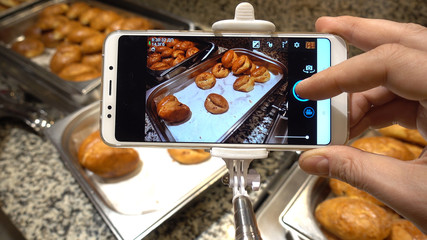 A man's hand holds a smartphone and makes photos of sweets. The concept of food photo for social networks. Buffet Restaurant.